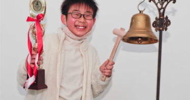 東京証券取引所から貸与された鐘を鳴らす小学生の部大賞の李 禮元さん